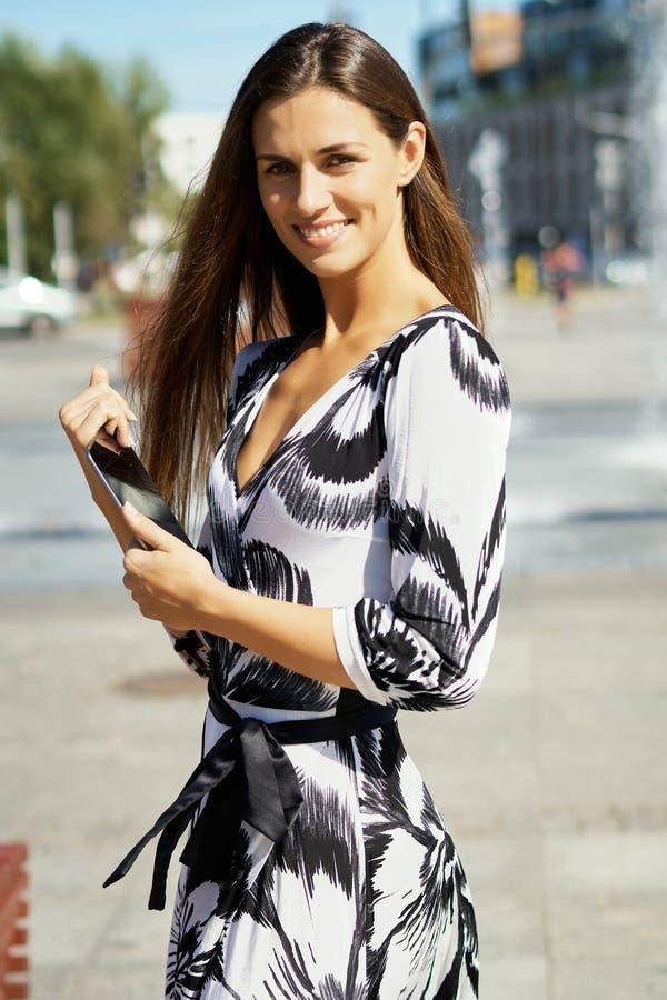 Piękna biznesowa kobieta z pastylką w ręka stojakach w pozach i parku obraz stock