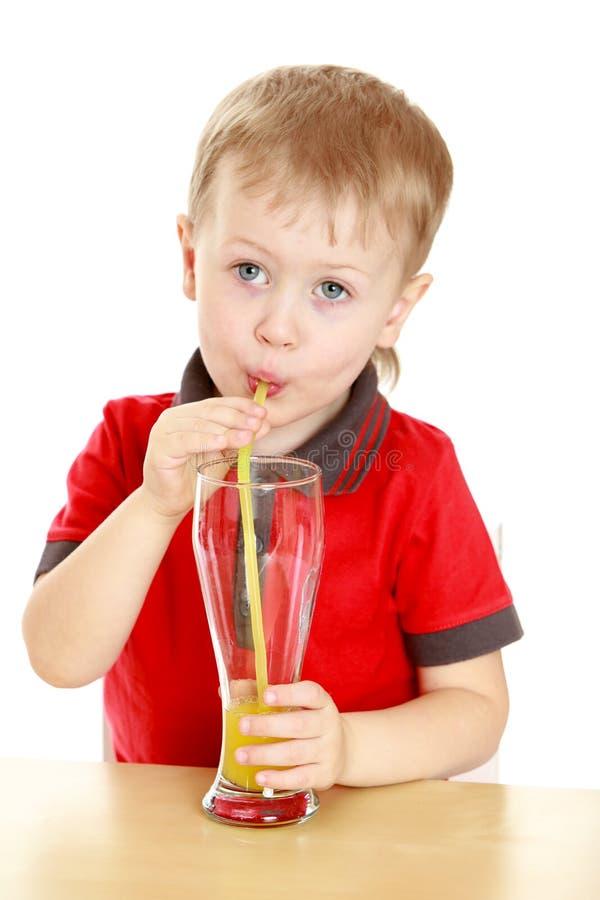 Piękna blond chłopiec pił przez słomy dużej zdjęcie stock