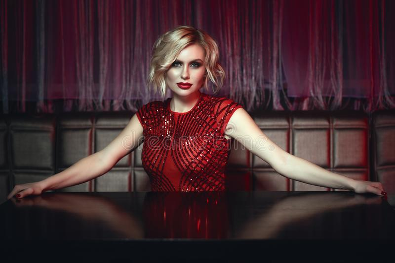 Piękna blond dama w czerwonym cekin sukni obsiadaniu przy pustym stołem w noc klubie czekać na rozkaz zdjęcie royalty free