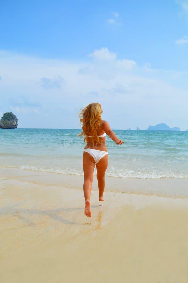 Piękna blond dziewczyna biega w ocean zdjęcia stock