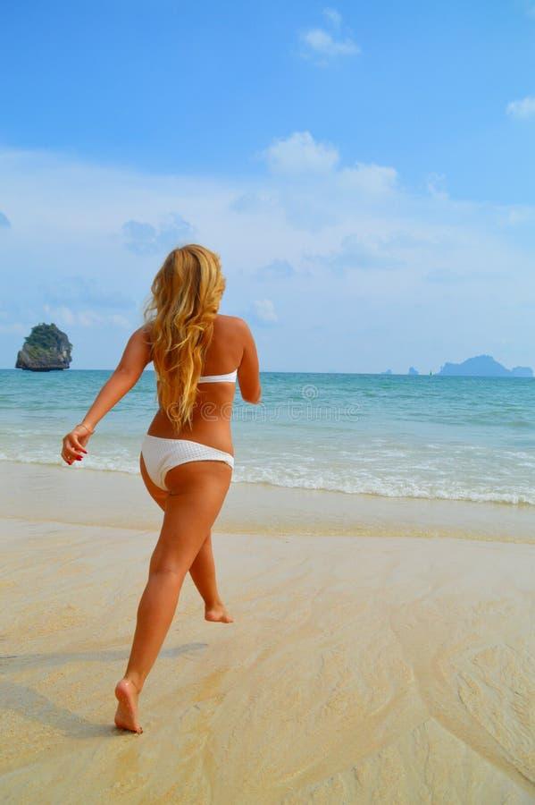 Piękna blond dziewczyna biega w ocean fotografia royalty free