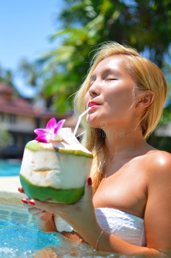 Piękna blond dziewczyna cieszy się koks w pływackim basenie zdjęcie royalty free