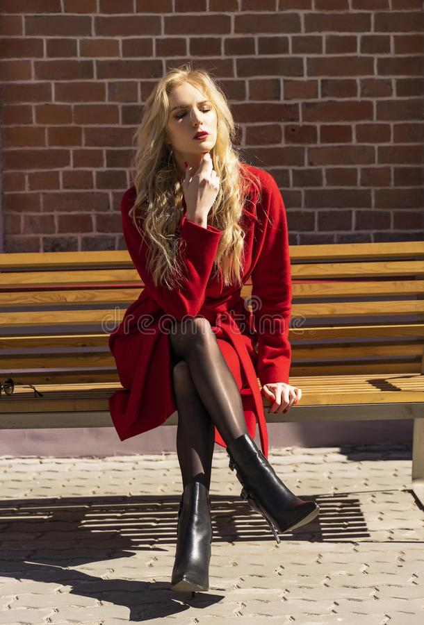 Piękna blond dziewczyna jest ubranym czerwonego żakiet i rękawiczki jest siedząca i odpoczywająca na ulicznej ławce blisko ściany fotografia stock