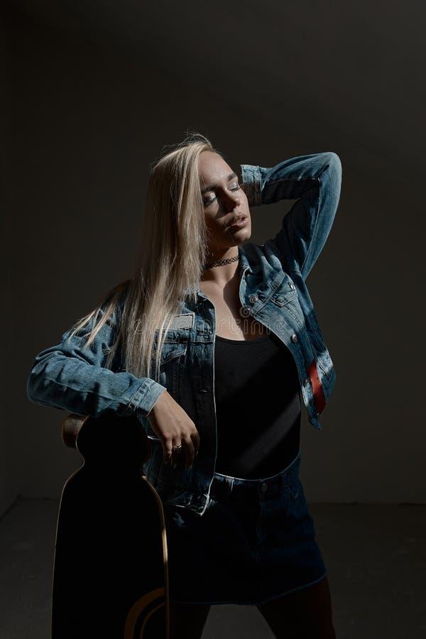 Piękna blond dziewczyna pozuje z loangboard zdjęcia stock