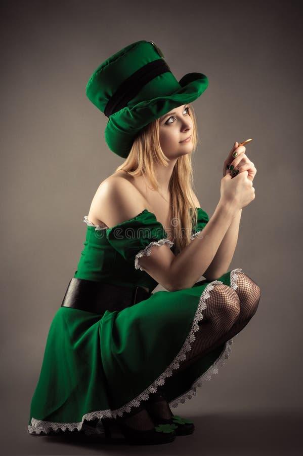 Piękna blond dziewczyna w leprechaun odzieżowym obsiadaniu z monetą zdjęcie royalty free