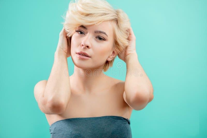 Piękna blond kobieta dotyka jej włosy na błękitnym tle z krótkim włosy zdjęcia stock
