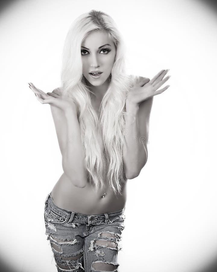 Piękna blond kobieta jest ubranym drelichowych cajgi zdjęcia stock