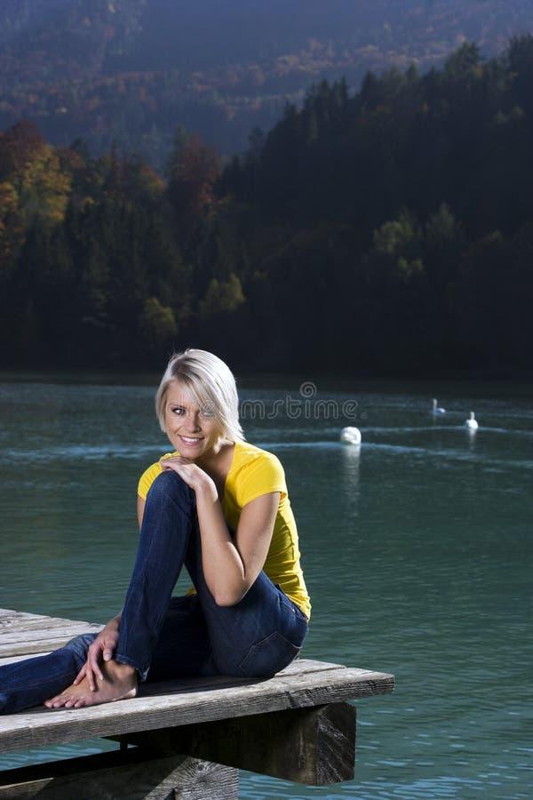 Piękna blond kobieta relaksuje przy jeziorem zdjęcia stock