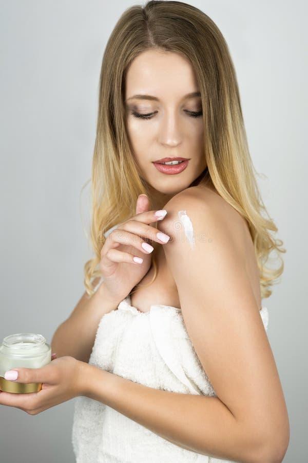 Piękna blond kobieta stosuje piękno śmietankę na jej ramieniu odizolowywał białego tło obraz stock