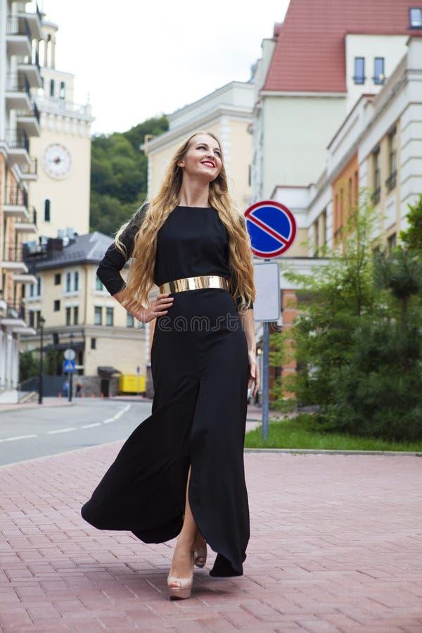 Piękna blond kobieta w długim smokingowym odprowadzeniu outdoors fotografia royalty free