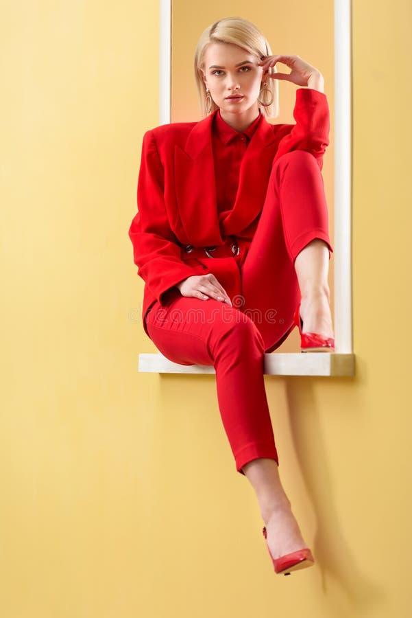 piękna blond kobieta w elegancki czerwony kostiumu i butów siedzieć zdjęcie stock