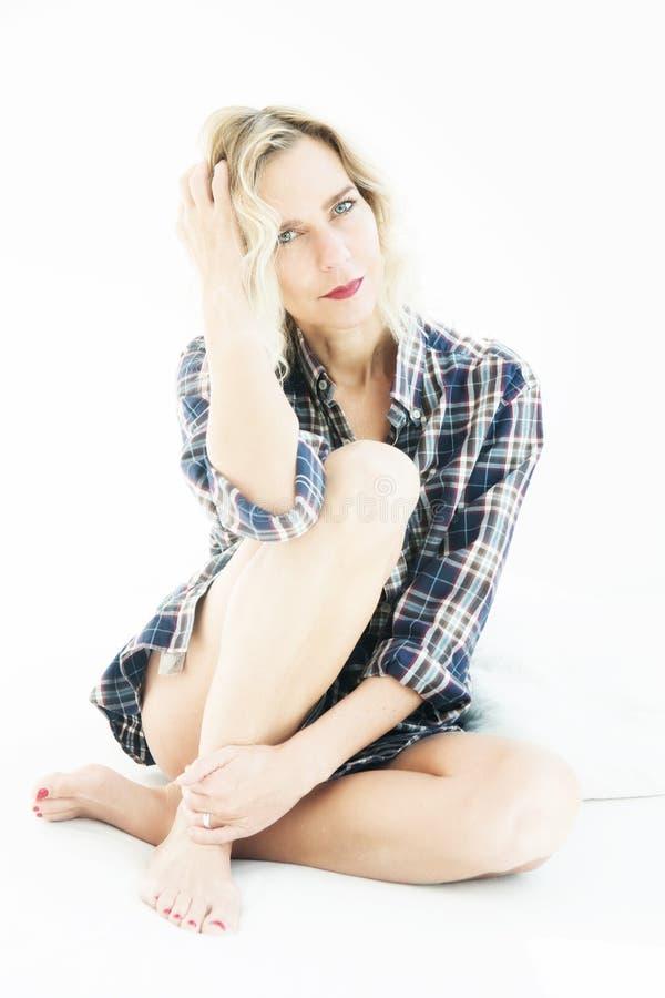 Piękna blond kobieta w koszulowym obsiadaniu w łóżku zdjęcia stock