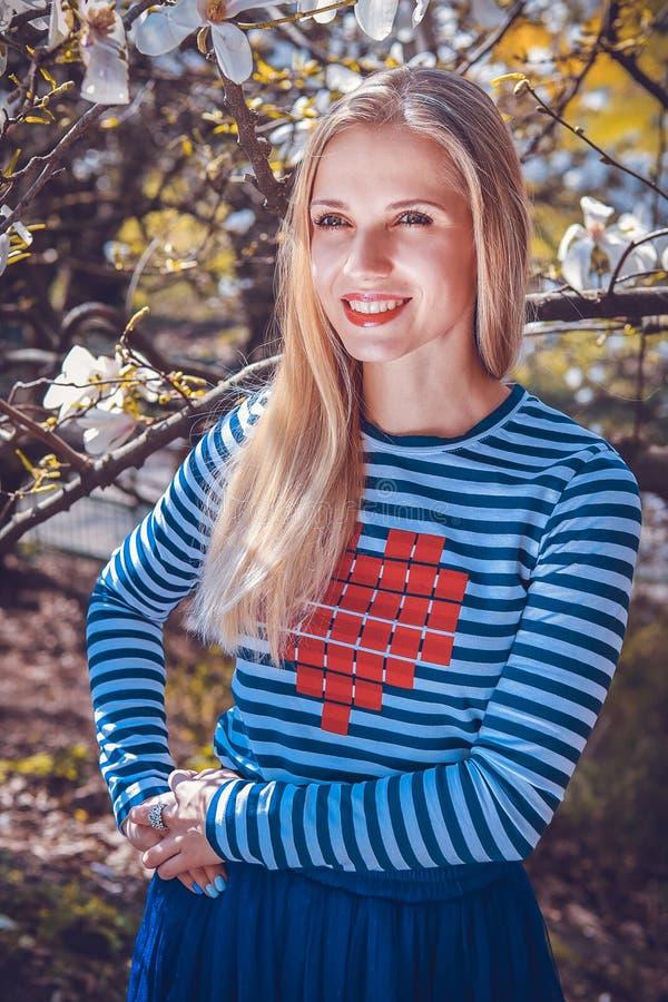 Piękna blond kobieta w parku Magnoliowi kwiaty fotografia royalty free