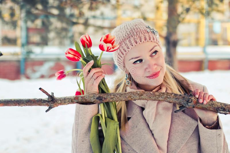 Piękna blond kobieta w zimie odziewa z czerwonymi tulipanami Portret szczęśliwa kobieta zdjęcie stock