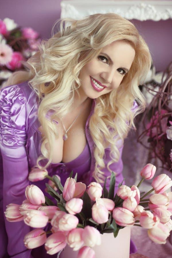 Piękna blond kobieta z długim falistym włosianym stylem w purpurowym dr zdjęcie stock