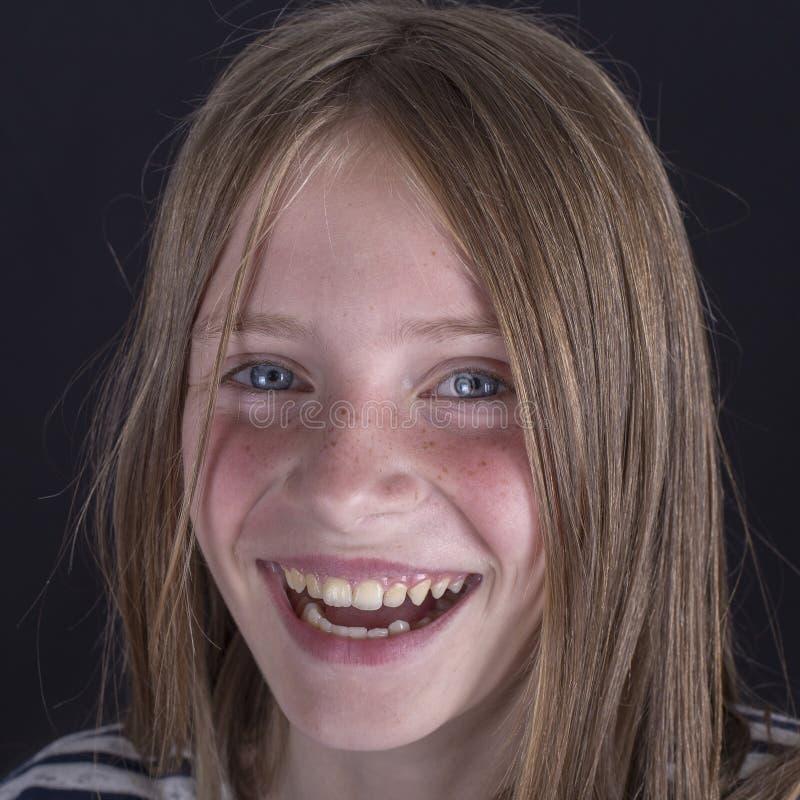 Piękna blond młoda dziewczyna z piegami indoors na czarnym tle, zbliżenie portret zdjęcie royalty free