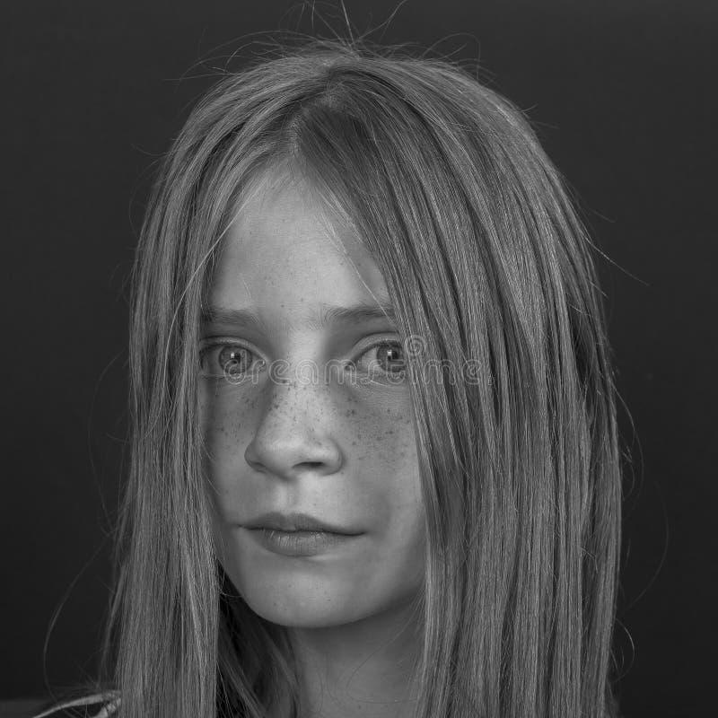 Piękna blond młoda dziewczyna z piegami indoors na czarnym tle, zbliżenie portret obrazy stock