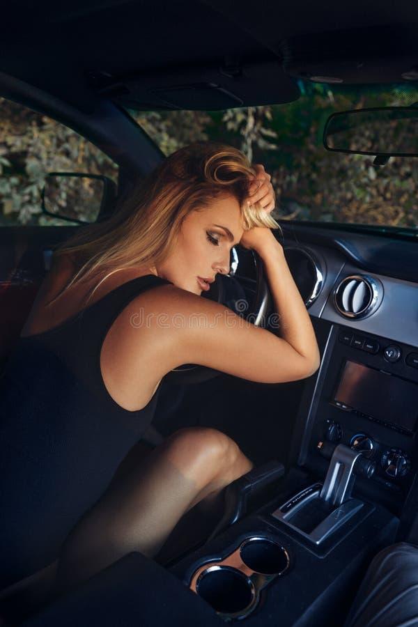 Piękna blond młoda kobieta w czarnym bodysuit obsiadaniu w samochodzie fotografia royalty free