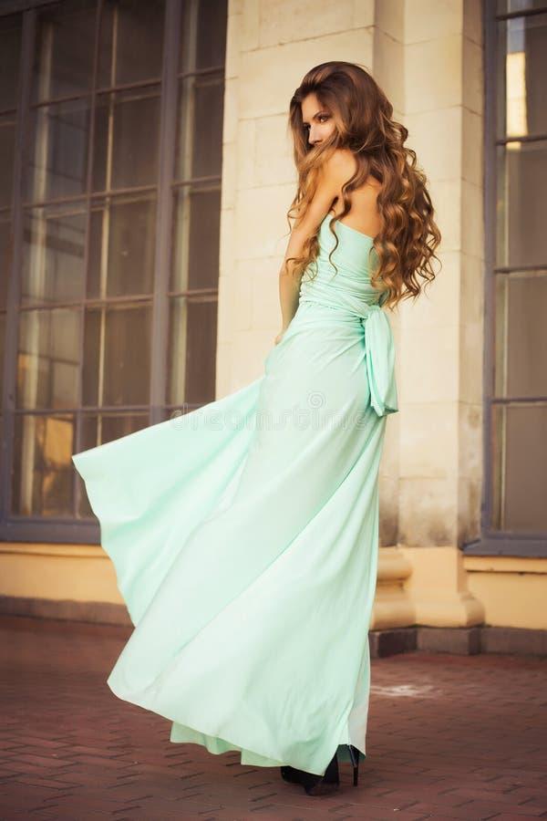 Piękna blondynka buduje wszystko w liściach z długim kędzierzawym włosy w długiej wieczór sukni w ruchu outdoors blisko retro roc zdjęcia royalty free