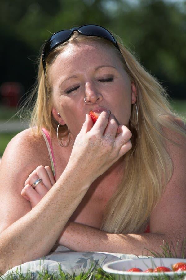 piękna blondynka cieszyć się świeże truskawki fotografia stock