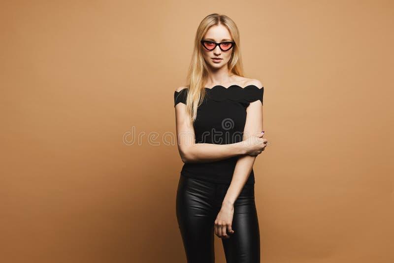 Piękna blondynka modela dziewczyna z seksownym ciałem w czarnych modnych skór spodniach w czarnej bluzce w modnych menchiach i obraz stock
