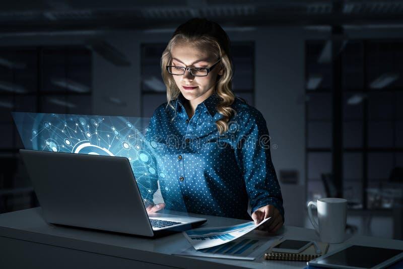 Piękna blondynka w ciemnym biurowym działaniu na laptopie i dostawać ne obrazy royalty free