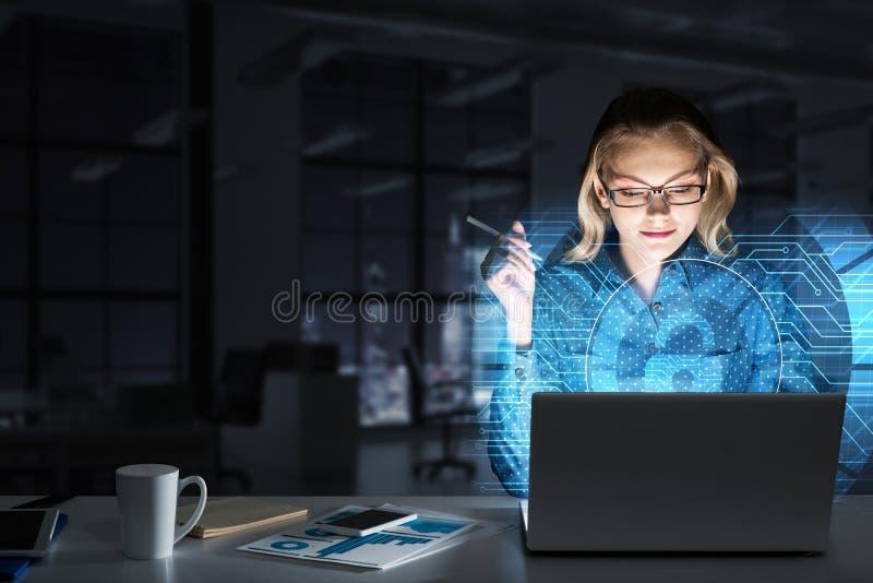 Piękna blondynka w ciemnym biurowym działaniu na laptopie i dostawać netto dostęp zdjęcia royalty free
