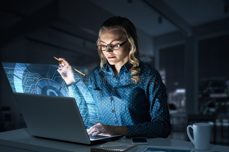 Piękna blondynka w ciemnym biurowym działaniu na laptopie i dostawać netto dostęp zdjęcie stock