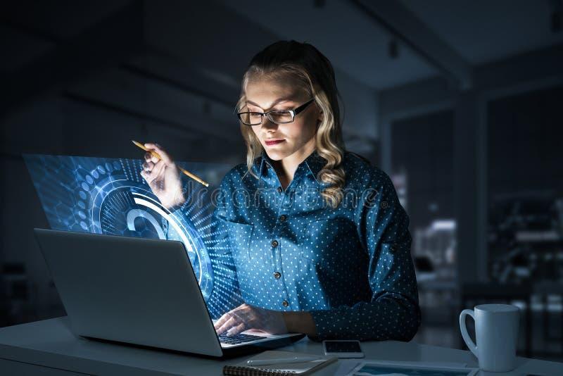 Piękna blondynka w ciemnym biurowym działaniu na laptopie i dostawać netto dostęp obraz royalty free