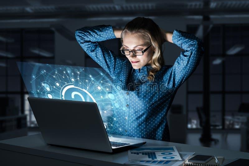 Piękna blondynka w ciemnym biurowym działaniu na laptopie i dostawać netto dostęp fotografia royalty free