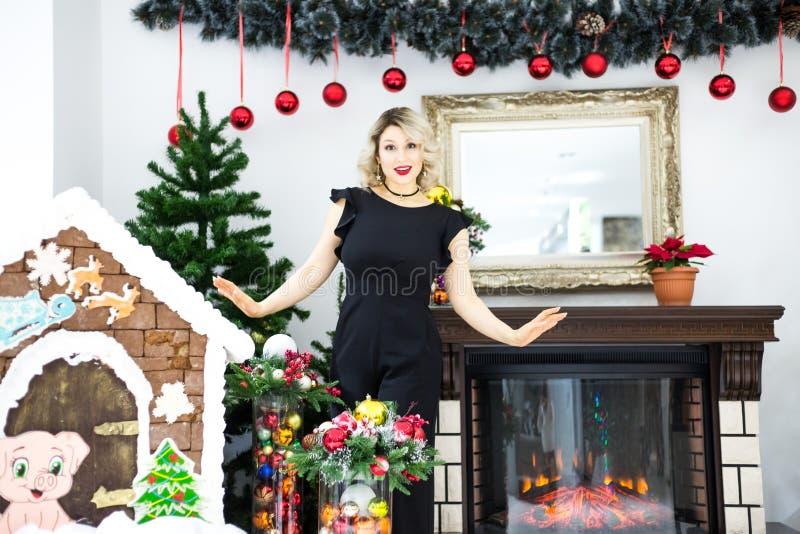 Piękna blondynka w czarnej sukni w nowy rok scenerii w fotografii studiu fotografia stock