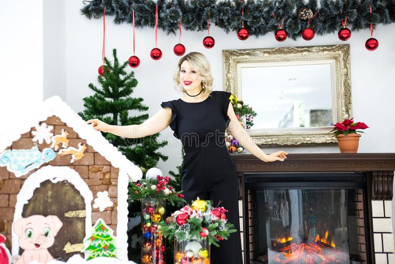 Piękna blondynka w czarnej sukni w nowy rok scenerii w fotografii studiu zdjęcia stock