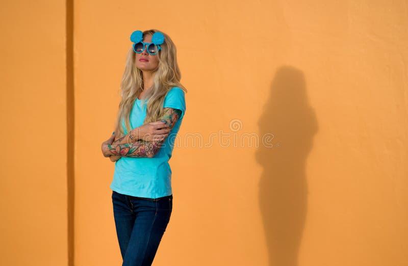 Piękna blondynka w okularach przeciwsłonecznych pozuje przy kamerą Portret na tle jaskrawa pomarańcze ściana Nowożytny modniś obrazy stock