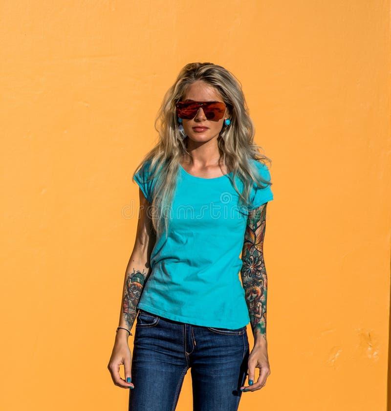 Piękna blondynka w okulary przeciwsłoneczni spojrzeniu przy kamerą Portret na tle jaskrawa pomarańcze ściana Nowożytna modniś dzi zdjęcia stock