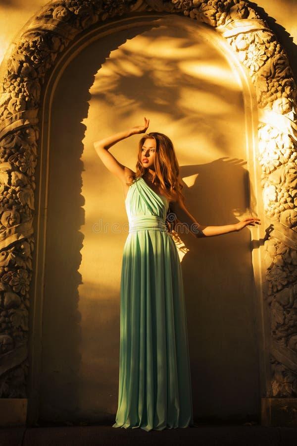 Piękna blondynka z długim kędzierzawym włosy w długiej wieczór sukni w ładunku elektrostatycznym outdoors blisko retro rocznika b obrazy stock