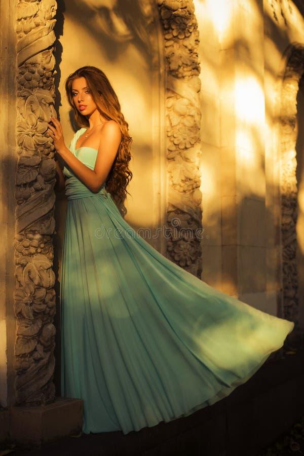 Piękna blondynka z długim kędzierzawym włosy w długiej wieczór sukni w ładunku elektrostatycznym outdoors blisko retro rocznika b fotografia royalty free