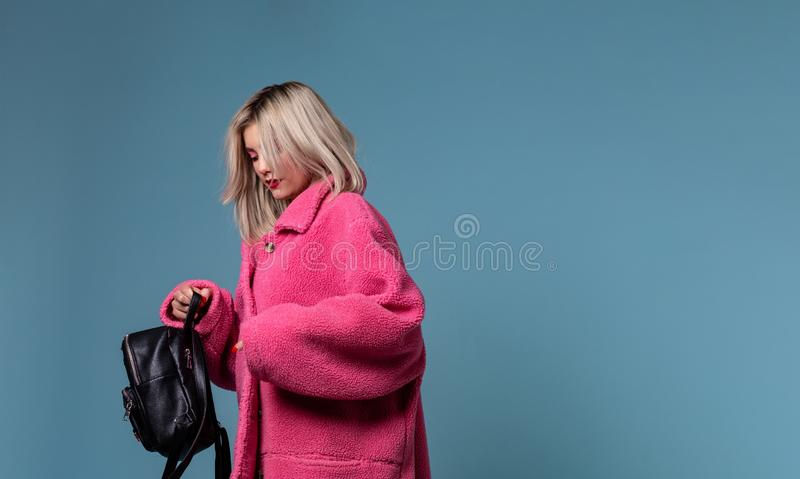 Piękna blondynki dziewczyna jest ubranym menchie pokrywa trzymać czarnego plecaka w rękach fotografia stock