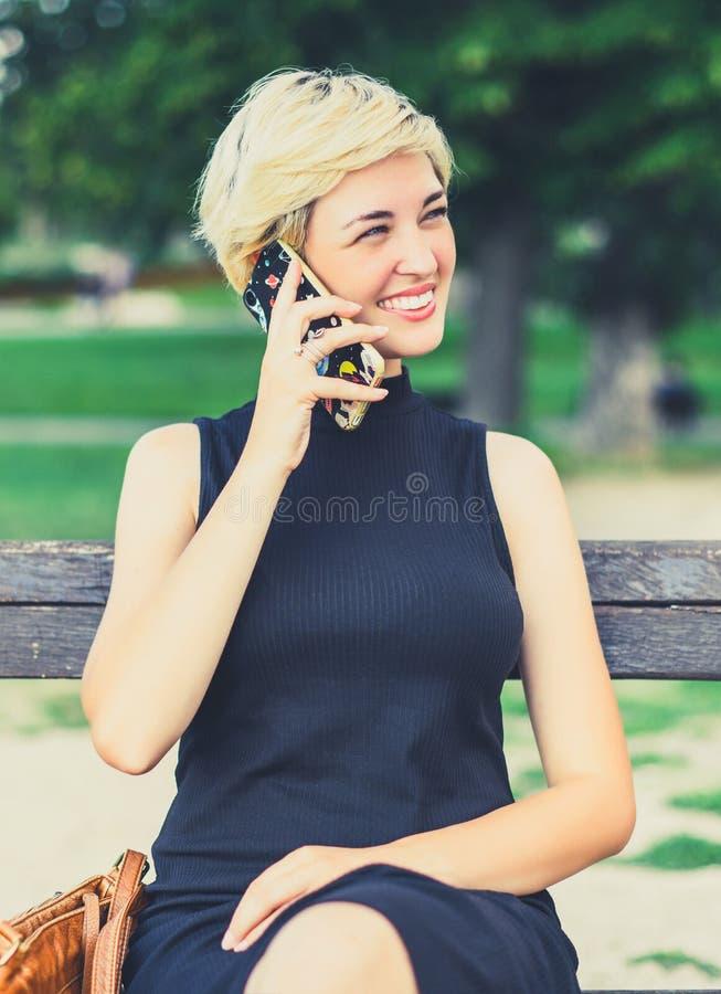Piękna blondynki dziewczyna opowiada na telefonie i ono uśmiecha się zdjęcie royalty free