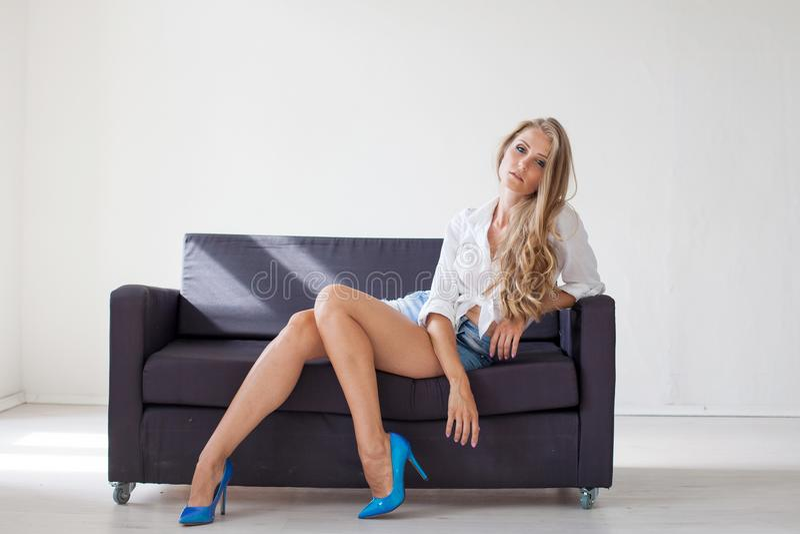 Piękna blondynki dziewczyna siedzi na leżance w białym pokoju 1 z niebieskimi oczami fotografia royalty free