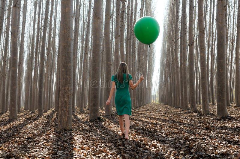 Piękna blondynki dziewczyna, ubierająca w zieleni, chodzi w las obraz stock