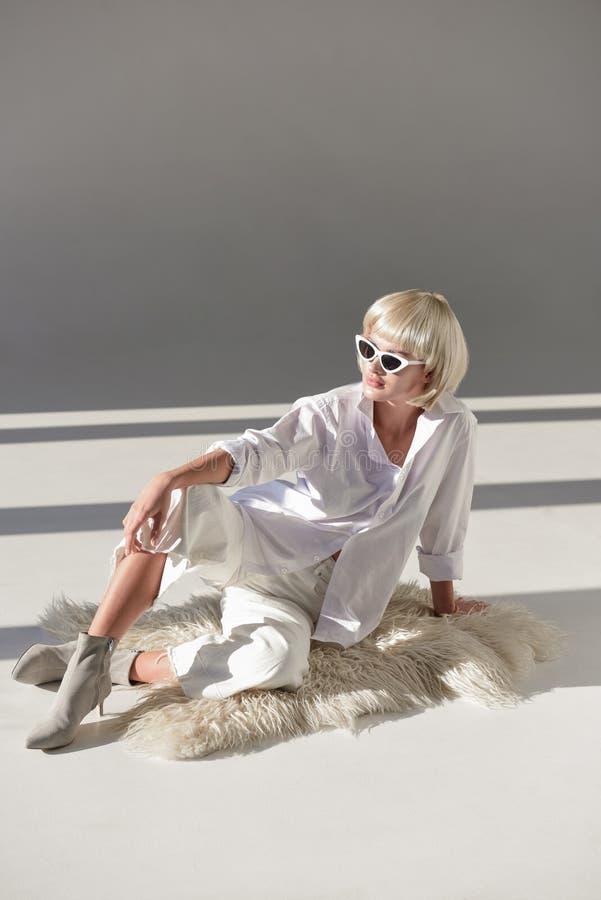 piękna blondynki dziewczyna w okularach przeciwsłonecznych i modny zima stroju obsiadanie na faux futerkowym żakiecie obrazy royalty free