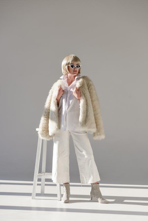 piękna blondynki dziewczyna w okularach przeciwsłonecznych i modnym zima stroju z faux futerkowego żakieta pozycją zdjęcie royalty free