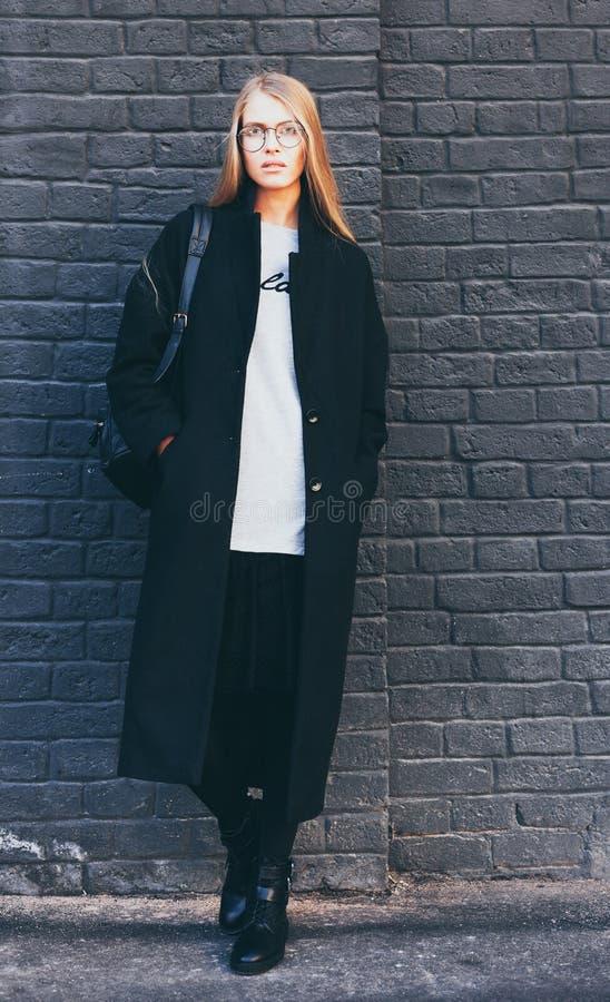 Piękna blondynki dziewczyna w round modnych szkłach w czarnym żakiecie i butach pozuje blisko czarnego ściana z cegieł Moda i obrazy royalty free