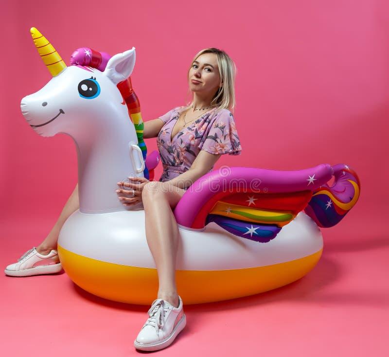 Piękna blondynki dziewczyna w seksowni sundress z szczupłymi nogami w białych sneakers siedzi na nadmuchiwanej barwiącej jednoroż zdjęcia royalty free