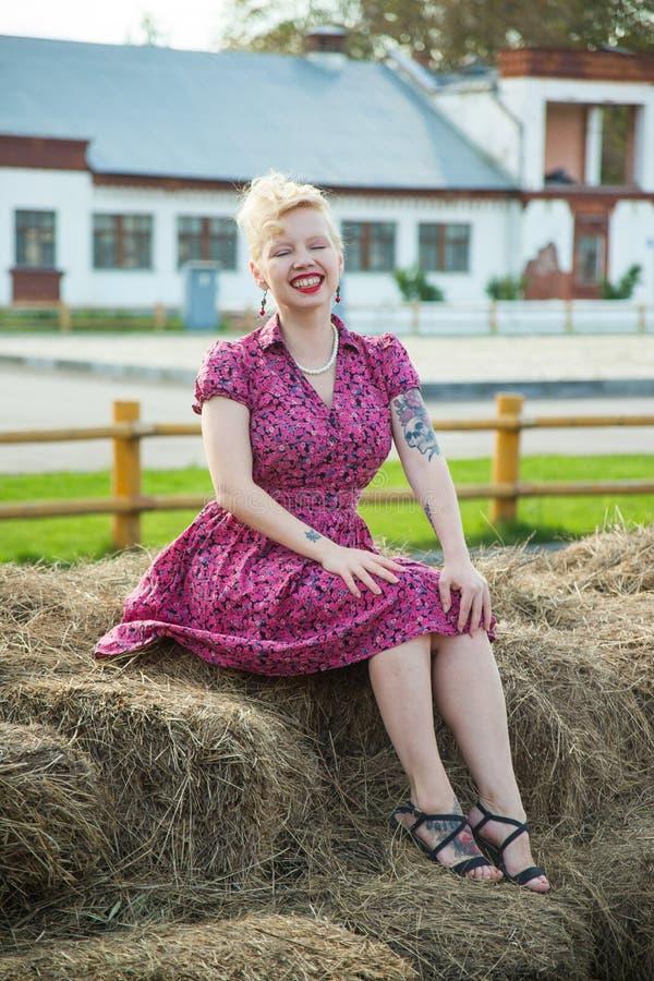 Piękna blondynki dziewczyna w szpilka stylu w jaskrawej sukni na sianie zdjęcia royalty free