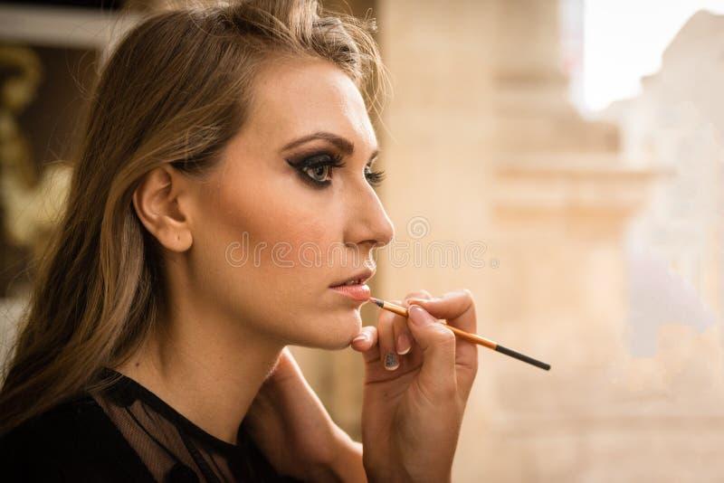 Piękna blondynki dziewczyna z dużymi niebieskimi oczami i czerń ubieramy, podczas zdjęcie royalty free