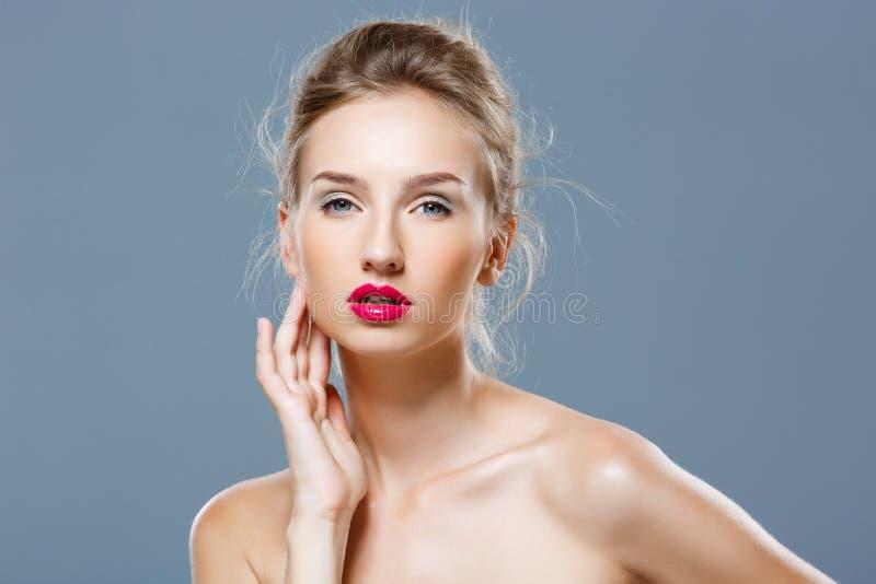Piękna blondynki dziewczyna z jaskrawym makeup pozuje nad popielatym tłem fotografia stock