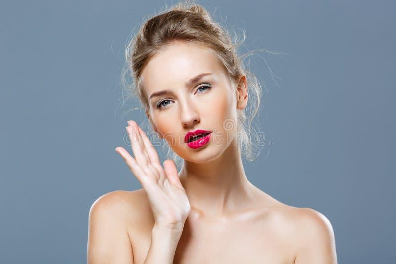 Piękna blondynki dziewczyna z jaskrawym makeup pozuje nad popielatym tłem zdjęcie royalty free