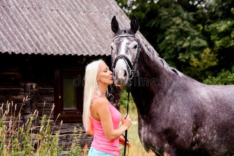 Piękna blondynki kobieta i jej koń w obszarze wiejskim obrazy stock