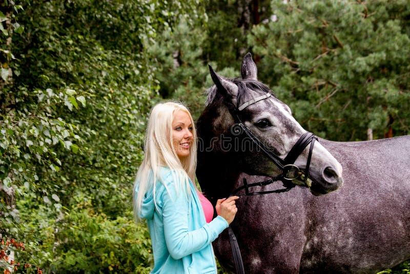 Piękna blondynki kobieta i jej koń w obszarze wiejskim fotografia stock